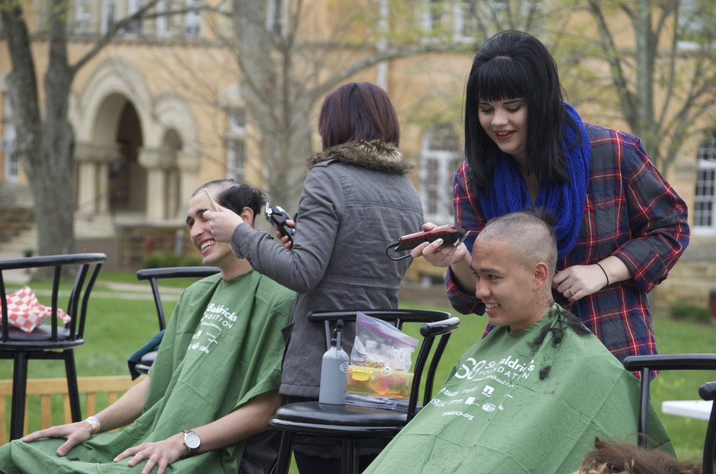 Giancarlo Vita '17 and Hank Tran '17 get their heads shaved in solidarity with childhood cancer patients.